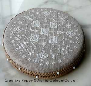 Round pinkeep with white lace cross stitch pattern by Agnès Delage-Calvet