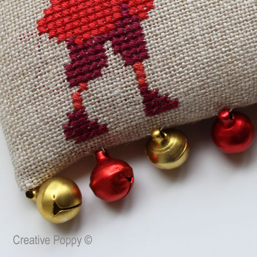 A row of small jingle bells stitched at the base of the cross stitch ornament