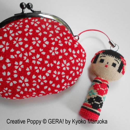 cross stitch kokeshi doll used as a charm on a bag