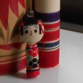 Close up on little cross stitched kokeshi doll